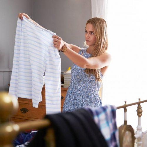 Frau räumt ihren Kleiderschrank aus