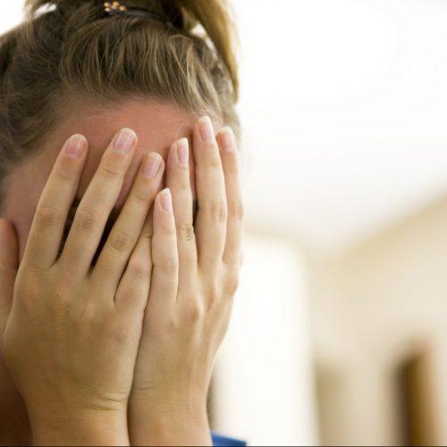 Frau schämt sich und hält die Hände vors Gesicht