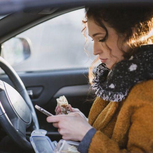 Frau mit Smartphone im Auto