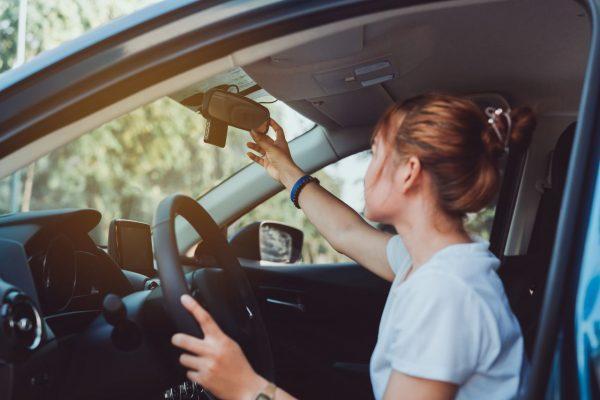 Frau sitzt im Auto und stellt Spiegel ein.