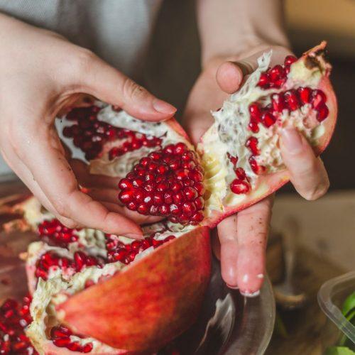 Frau öffnet Granatapfel