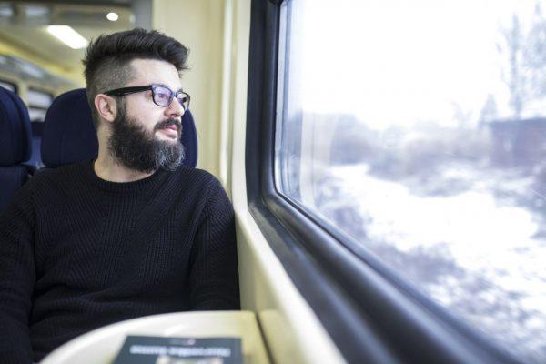 Langeweile: Mann schaut im Zug aus dem Fenster.