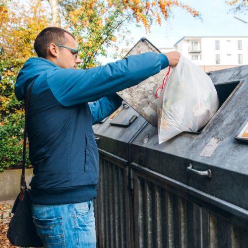 Mann an Mülleimer