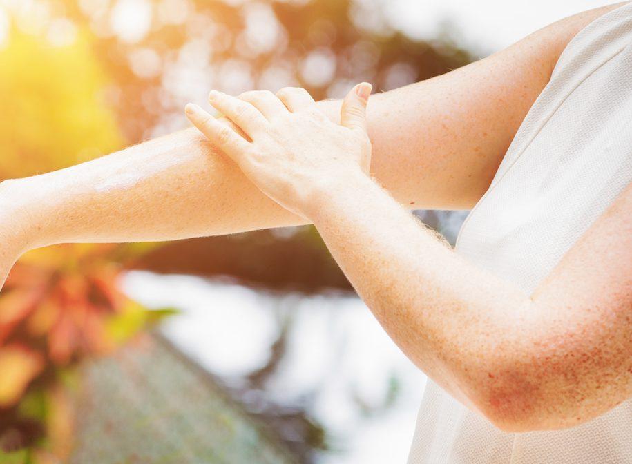 Eine junge Frau trägt Creme auf den Arm auf