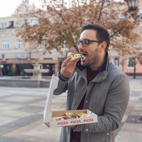 Mann isst im Stehen