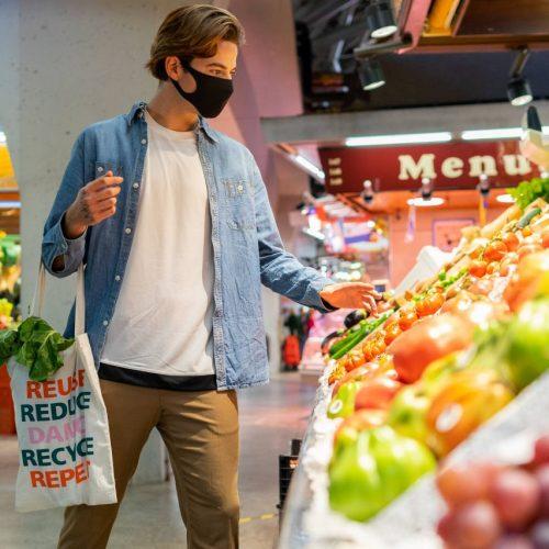 Mann kauft mit Jutebeutel im Gemüse