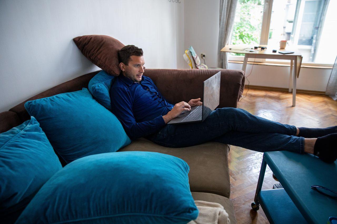 Junger Mann im Videocall auf dem Sofa