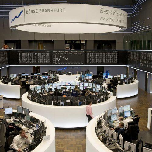 Die Frankfurter Börse an einem Handelstag. Der DAX-Kurs im Hintergrund, im Vordergrund die Broker.