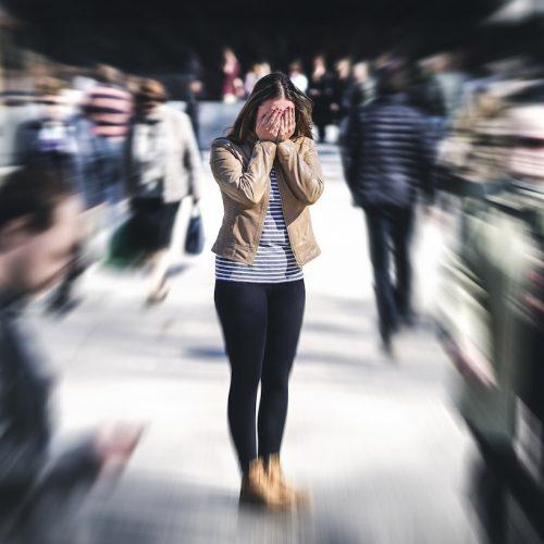 Eine Frau erleidet in der Öffentlichkeit eine Panikattacke, mögliches Symptom der Schizophrennie.