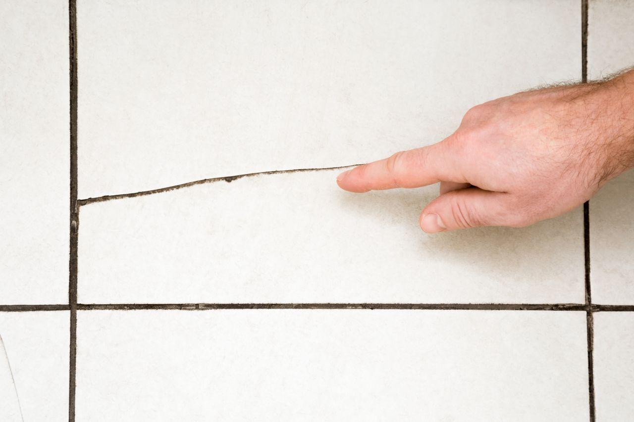 Hand zeigt auf Riss in der Fliese