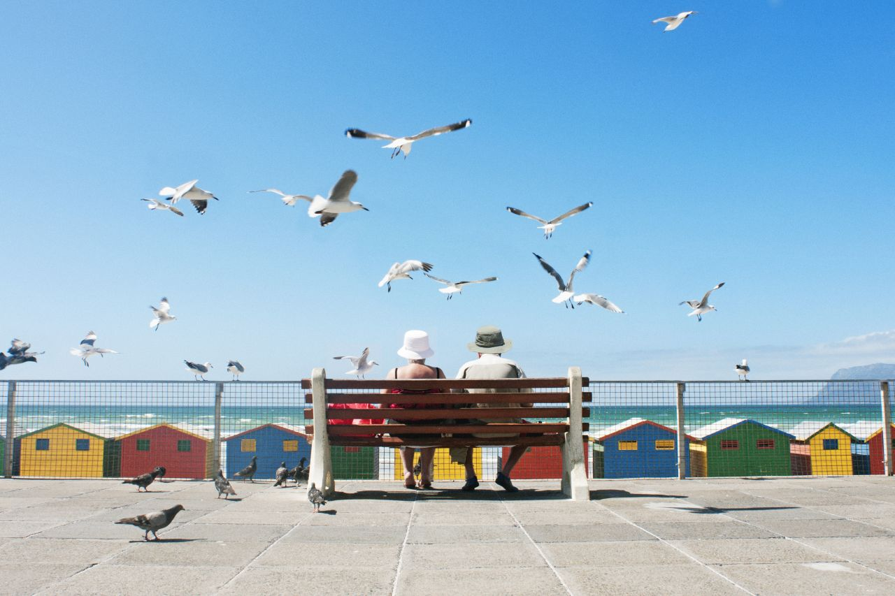 Senioren sitzen auf Bank am Meer