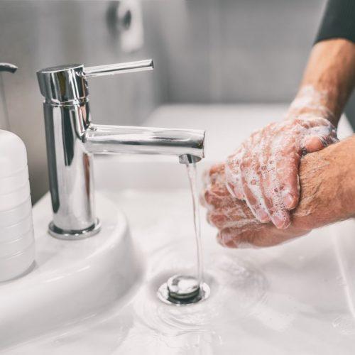 Männerhände unter laufendem Wasserhahn