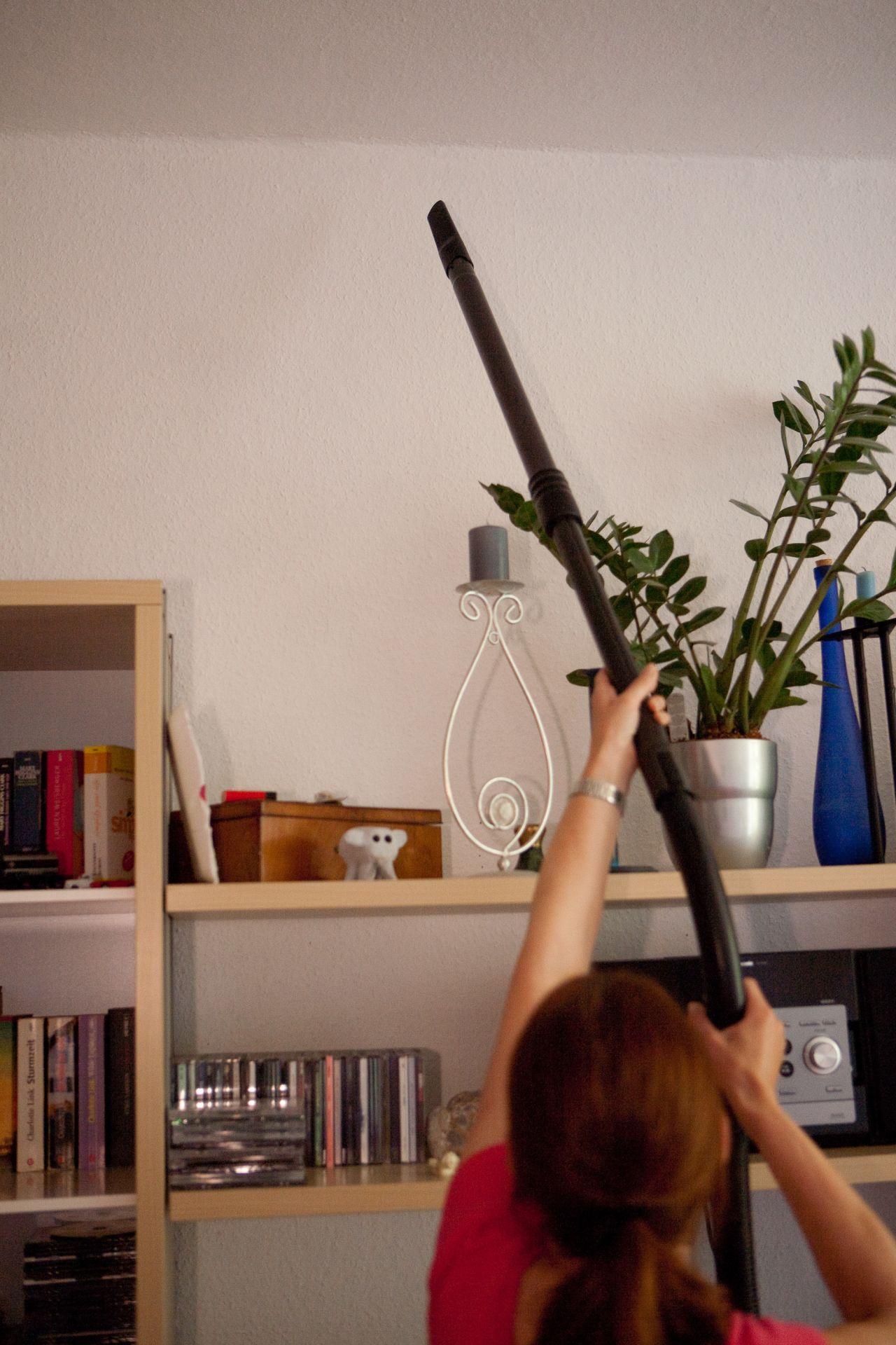 Frau fängt Spinne mit dem Staubsauger