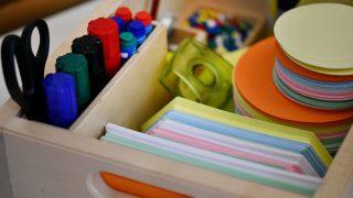Eine Kiste mit Büromaterial wie Stiften, Tesa und Notizzetteln.
