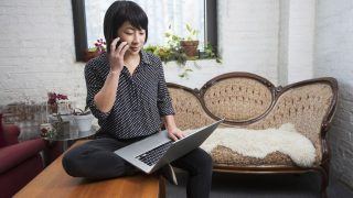 Eine Frau telefoniert mit dem Handy, auf ihrem Schoss ist ein Laptop.