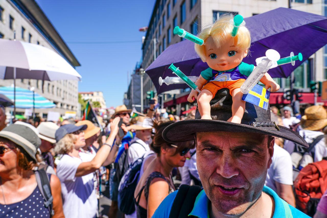 Anti-Corona-Demonstrant mit einer Puppe voller Spritzen auf dem Hut - als Zeichen gegen die Impfung