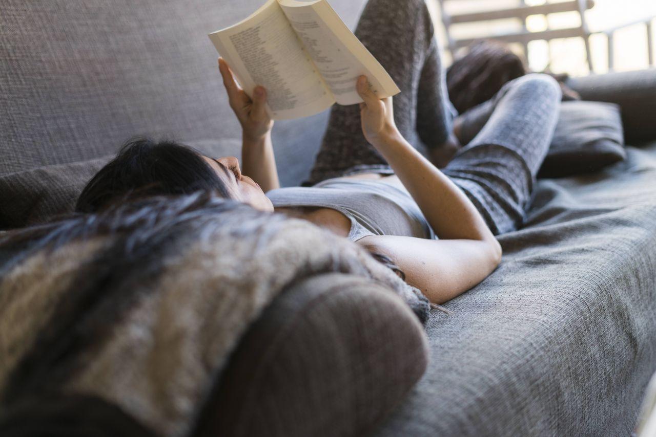 Frau entspannt auf dem Sofa und liest ein Buch