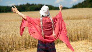 Frau steht in Kornkreis und meditiert