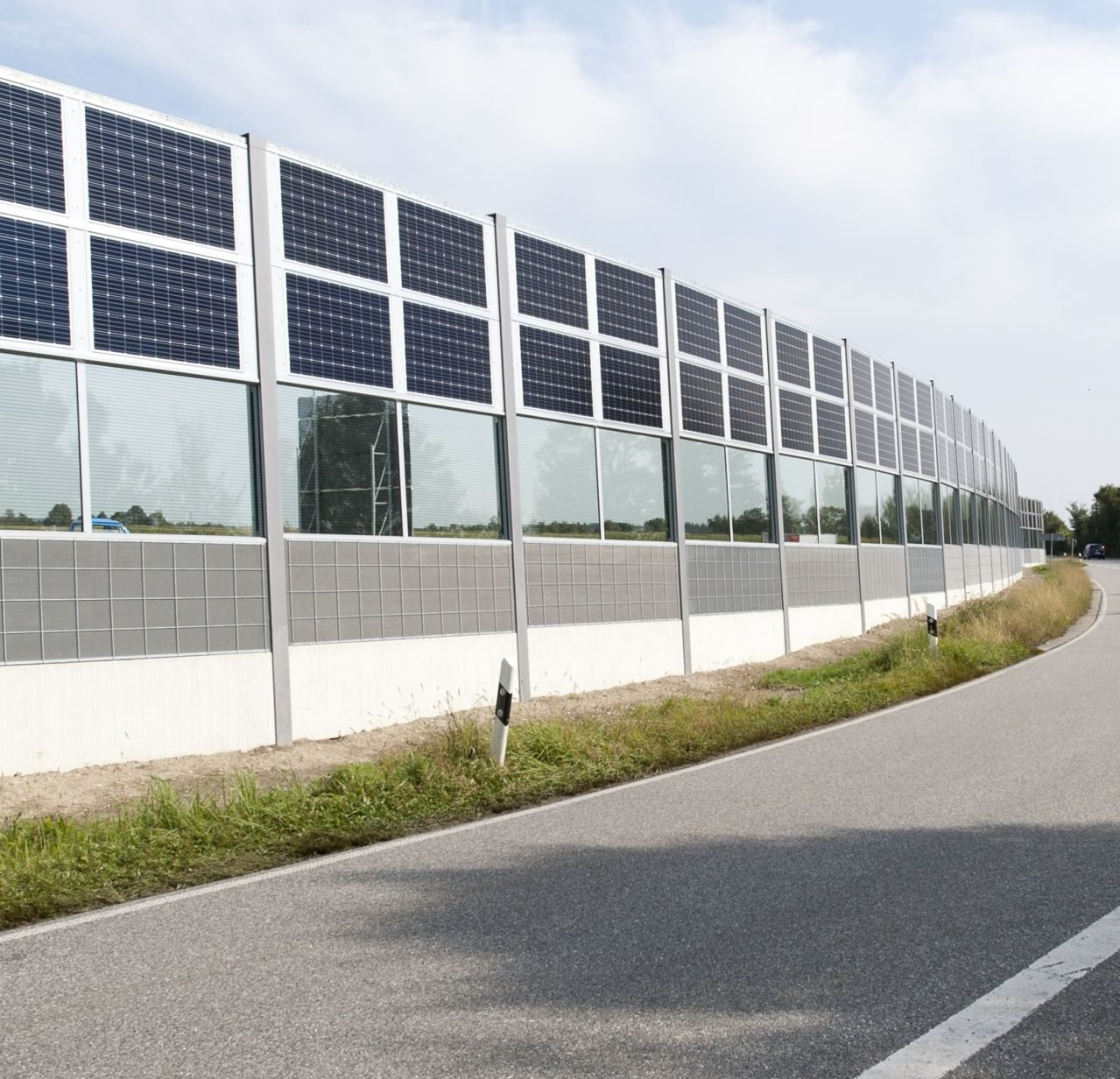 Massive Lärmschutzwand mit teiltransparenter Ausführung und Standard-PV-Modulen
