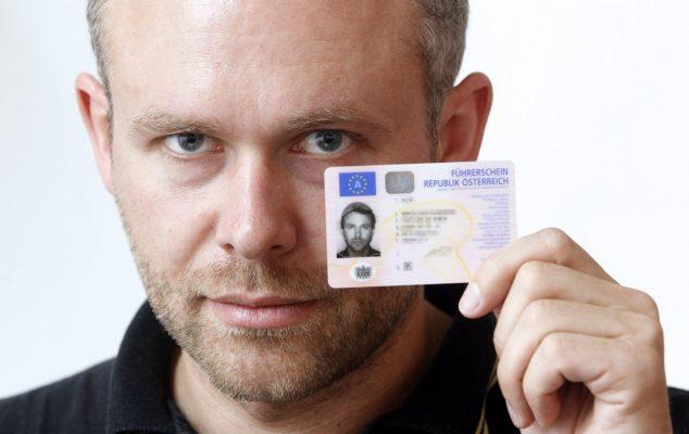 Niko Alm zeigt seinen Führerschein, mitsamt dem Nudelsieb auf seinem Kopf.