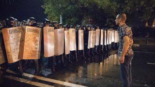 Ein Demonstrant stellt sich der Polizei entgegen.