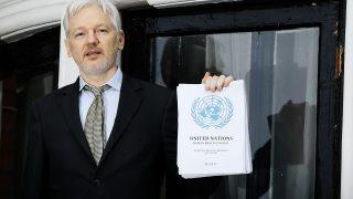 Julian Assange mit dem Bericht der UN in der Hand.