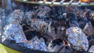 In Alufolie eingewickelte Kartoffeln auf dem Grill.