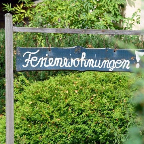 """Ein Schild """"Ferienwohnungen!"""" steht vor einem Haus. Die Bundesländer haben ein Beherbergungsverbot für Urlauber aus inländischen Corona-Risikogebieten beschlossen."""