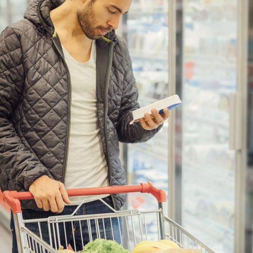 Mann schaut im Supermarkt auf die Inhaltsstoffe