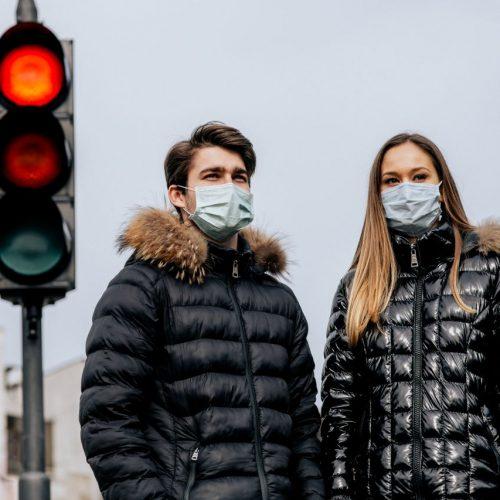 Mann und Frau mit Maske stehend vor einer roten Ampel