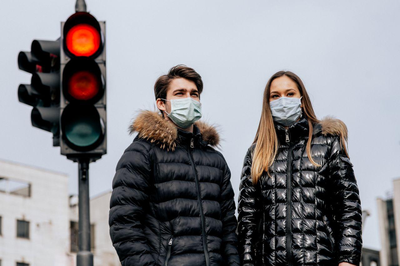 Paar mit Mundschutz vor Ampel