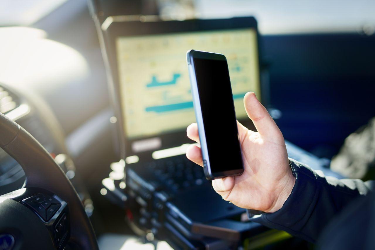 Polizist hält Handy