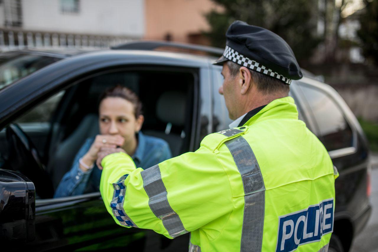 Polizist führt einen Atemalkoholtest bei einer Autofahrerin durch.