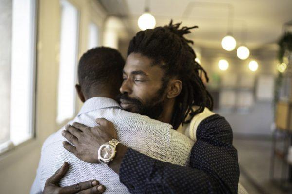 Zwei Männer umarmen sich innig