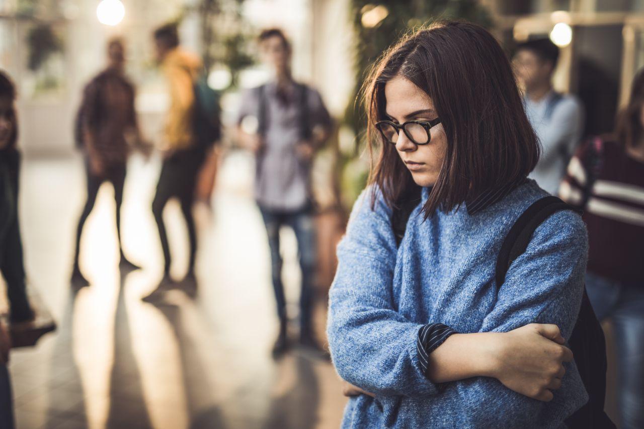 Eine Frau steht alleine und traurig, abseits von der Menge.