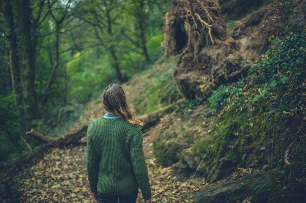 Eine Frau steht alleine im Wald.