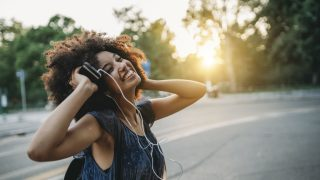 Eine Frau hört glücklich mit Kopfhörern Musik, während die Sonne untergeht.