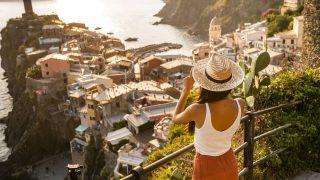 Eine Frau steht mit Sonnenhut vor einer Stadt am Meer, während die Sonne untergeht.