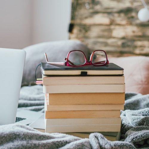 Ein Stapel Bücher auf dem Bett.