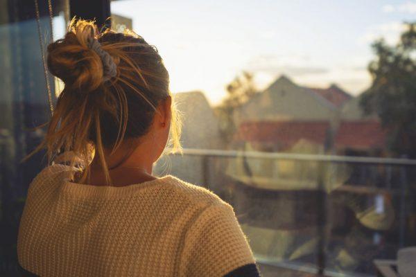 Frau von hinten am Fenster (Getty Images)