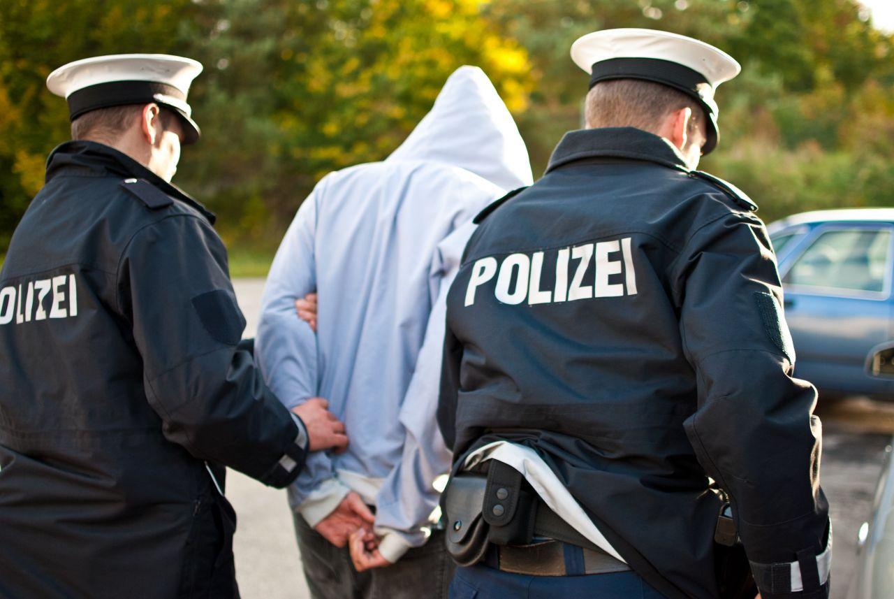 2 Polizisten führen eine Person in Handschellen ab.