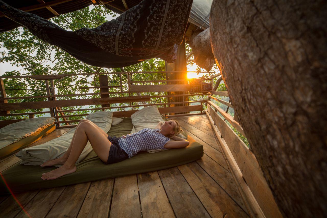 Frau entspannt im Baumhaus