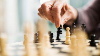 Eine Person macht einen Zug auf einem Schachbrett.