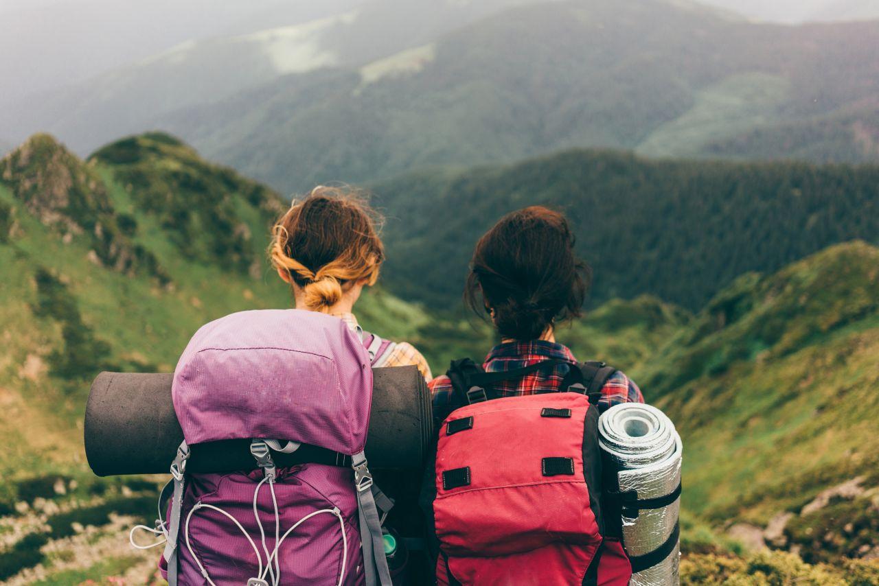 Zwei Frauen stehen mit Reiserucksäcken in den Bergen und genießen die Aussicht.