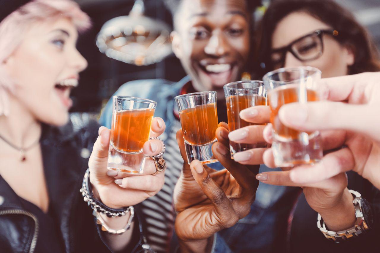 Freunde stoßen zusammen mit einem Glas Schnaps an.