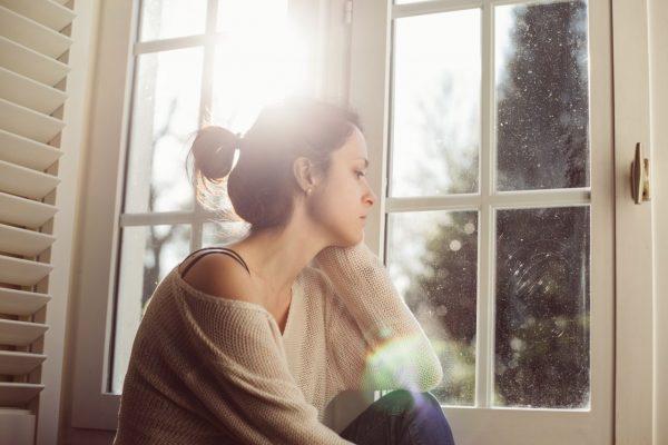 Eine Frau schaut traurig aus dem Fenster