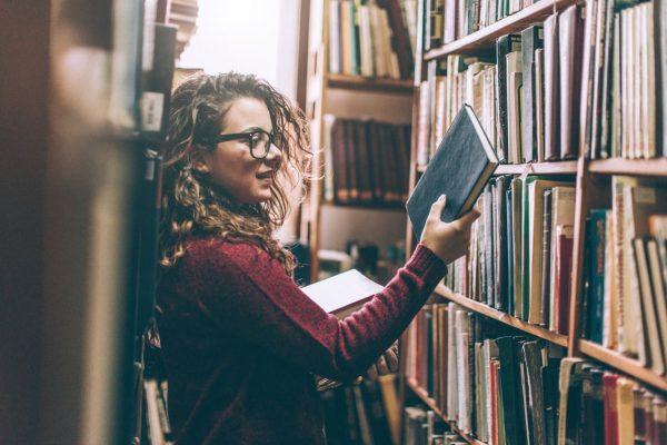 Eine Frau schaut sich ein Buch in einer Bibliothek an