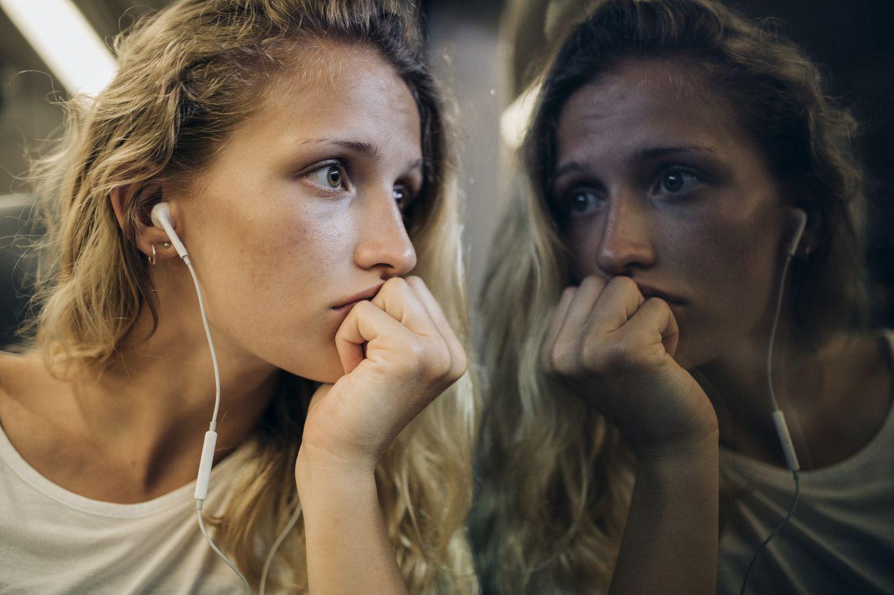 Eine junge Frau schaut traurig aus demZugfenster und hört dabei Musik.