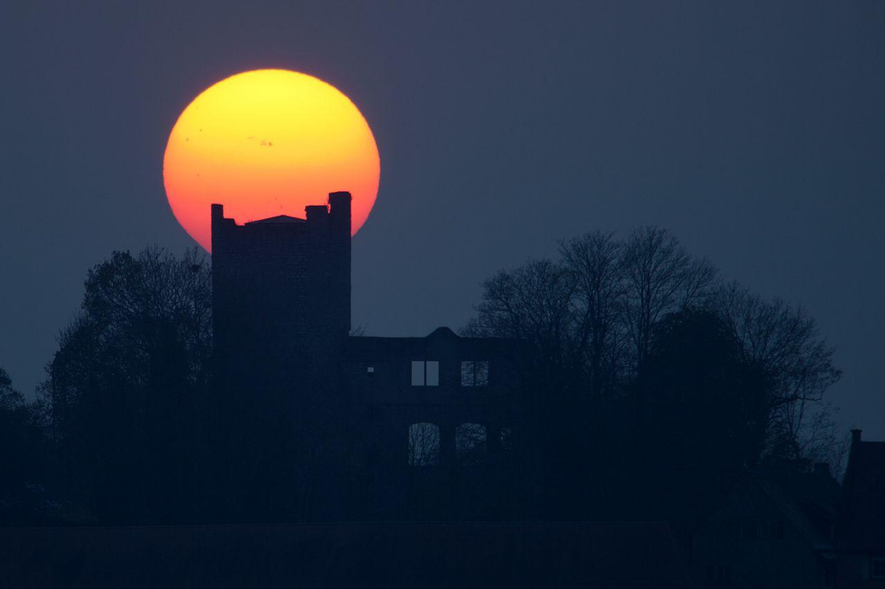 Wenn die Sonne tief steht, lassen sich Sonnenflecken manchmal mit dem bloßen Auge erkennen (Achtung: Nie direkt oder ohne Filter in die Sonne schauen!).