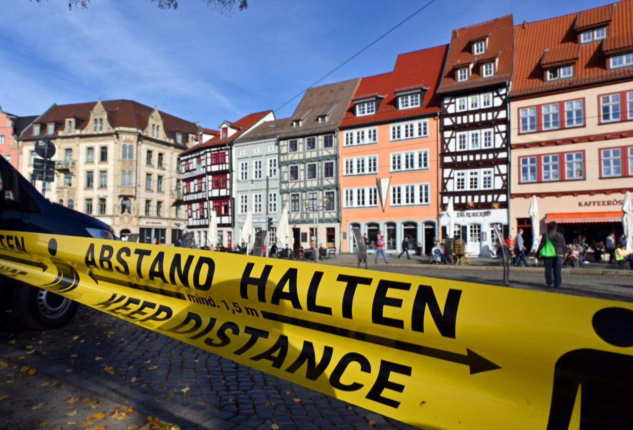 """Thüringen, Erfurt: """"Abstand halten!"""" steht auf einem Flatterband am Domplatz inmitten der Altstadt. Zahlreiche Städte und Kreise haben die Grenze von 50 Neuinfektionen pro 100.000 Einwohner innerhalb von 7 Tagen überschritten - und gelten als Risikogebiete."""
